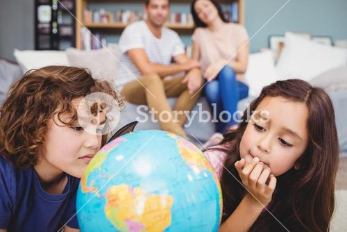 Close-up of children looking at globe
