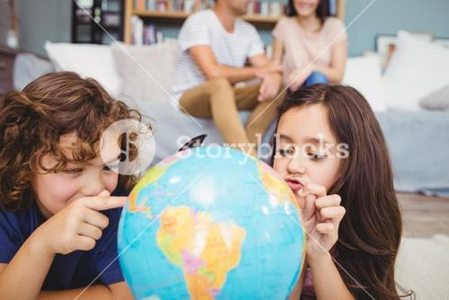 Children pointing at globe while parents in background