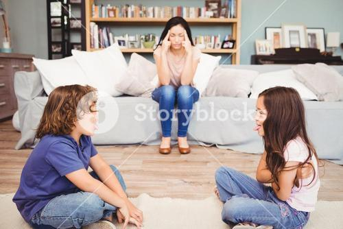 Children playing while mother sitting on sofa