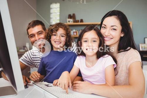 Portrait of happy family sitting by computer