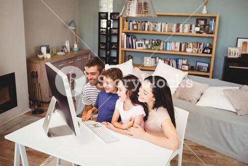 Happy family using computer at home