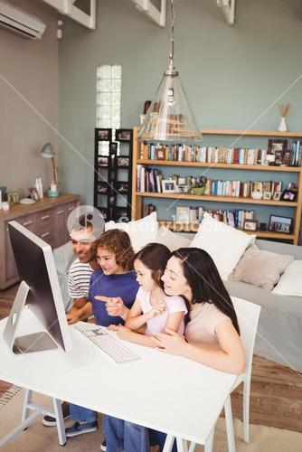 Cheerful family using computer at home