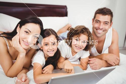 Portrait of happy children with parents using laptop on bed