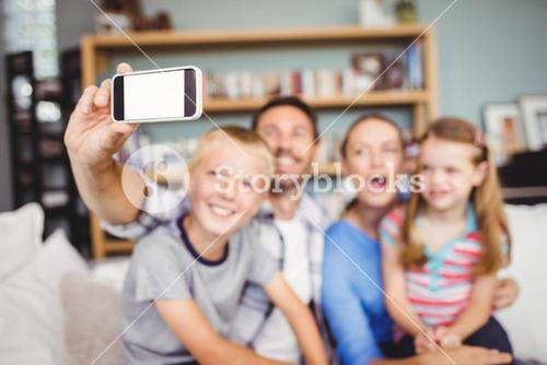 Man taking selfie of family with mobile phone