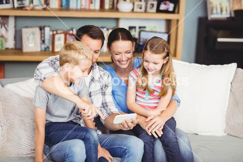 Family using mobile phone while sitting on sofa