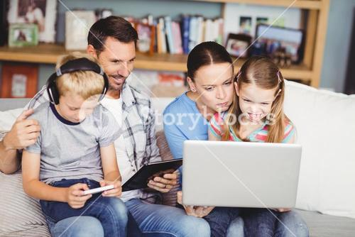 Family using technologies on sofa