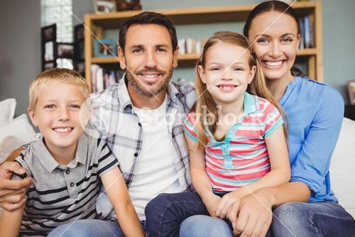 Cheerful family sitting on sofa in living room
