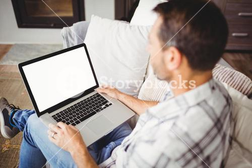 Man using laptop while sitting on sofa at home