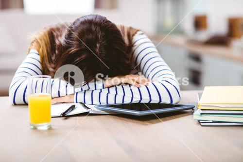 Woman napping with head by digital tablet and books