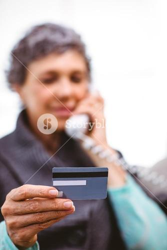 Mature woman holding payment card while talking on telephone