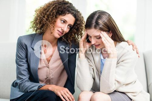 Psychologist counselling depressed woman at home