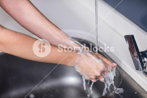 Cropped image of woman rinsing hands