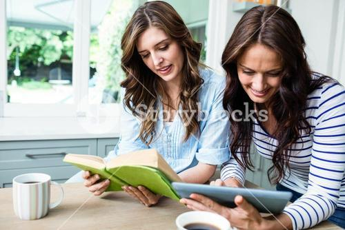 Female friends using digital tablet and reading book