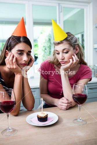 Sad friends with hand on chin while sitting at table during birthday party