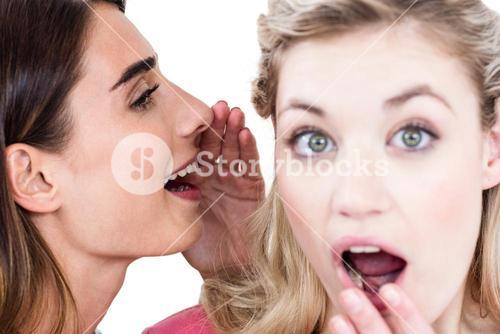 Close-up of woman whispering in friend ear