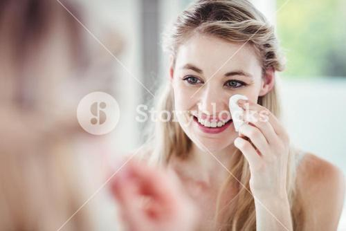 Happy young woman applying blush