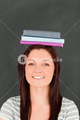 Portrait of a smilling young woman wearing books on her head