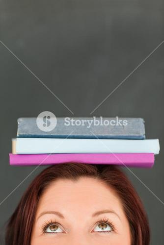 Happy young woman wearing books on her head