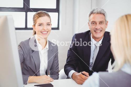 Smart business people sitting at desk in office