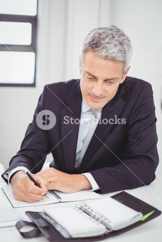 Businessman writing in spiral notebook in office