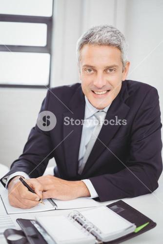 Happy businessman writing in spiral notebook