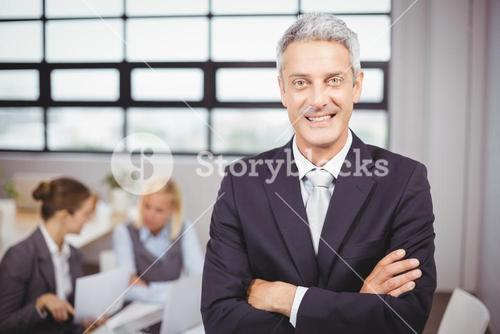 Happy confidence businessman with colleagues in background