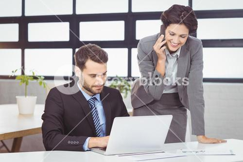 Business people with mobile phone and laptop in office
