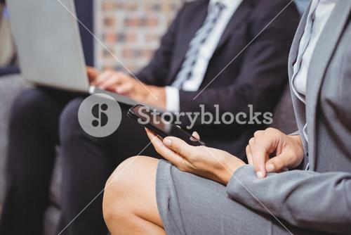 Midsection of business people using mobile phone and laptop