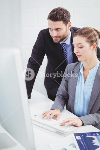 Businessman looking in computer monitor while colleague typing