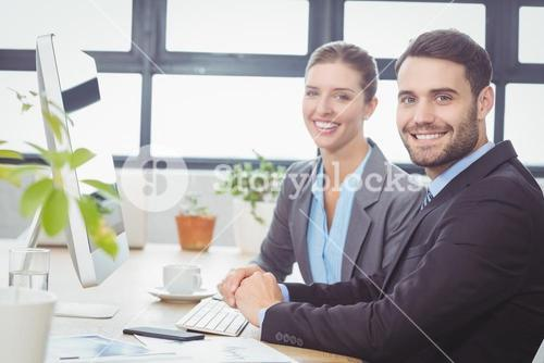 Happy business people working at computer at desk