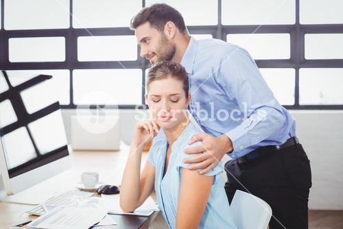 Businessman harassing female colleague at computer desk