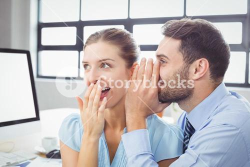 Happy businessman whispering to female colleague