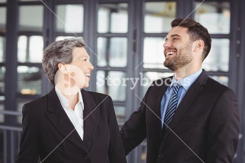Business people laughing while standing in office