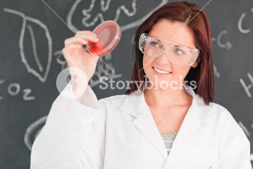 Redhaired scientist holding a petri dish