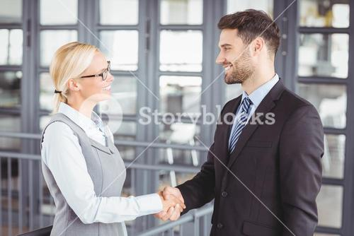 Business people handshaking while standing in office