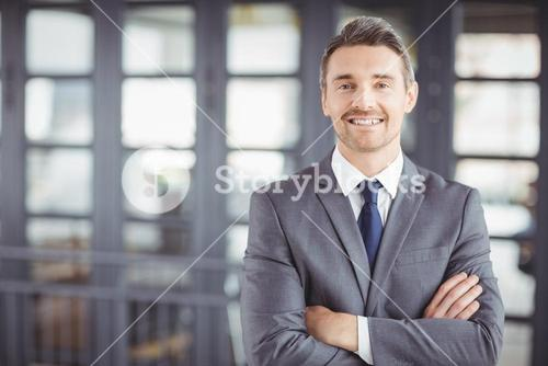 Smiling businessman with arms crossed in office