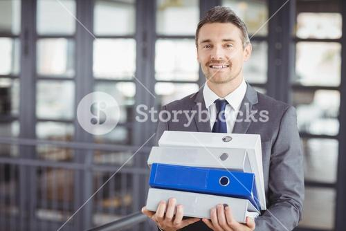 Businessman carrying files stack in office