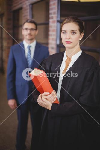 Female lawyer with businessman standing in background