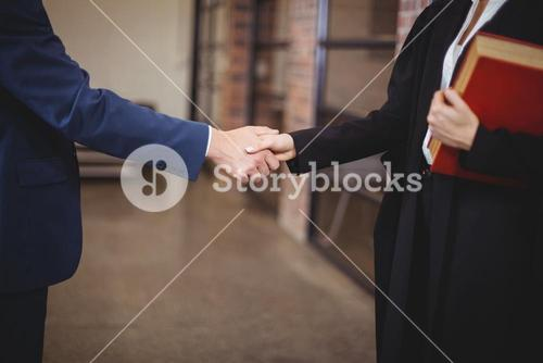 Midsection of female lawyer handshaking with client