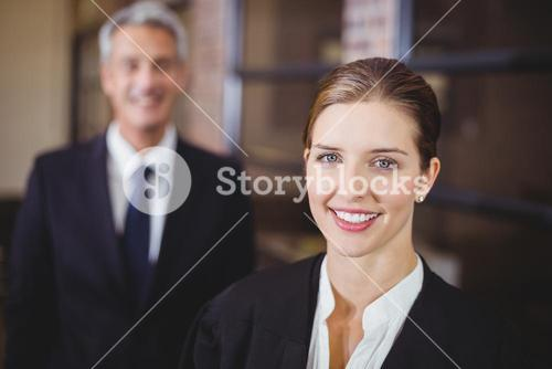 Female lawyer smiling while male colleague in background