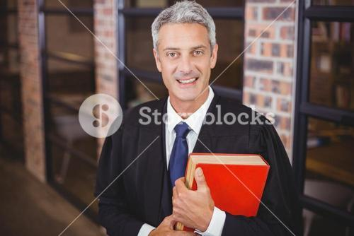 Male lawyer standing with red book at office