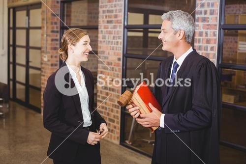 Male lawyer smiling while discussing with female colleague