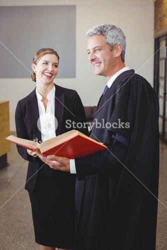 Male lawyer with book standing by female colleague