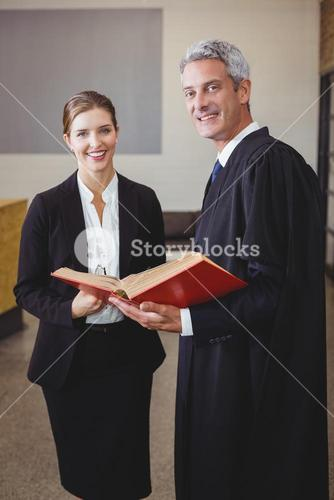 Male lawyer holding book while standing with female colleague