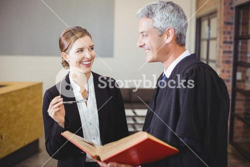 Happy Male lawyer standing by female colleague