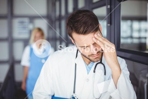 Male doctor suffering from headache