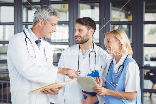 Senior doctor discussing with coworkers while standing
