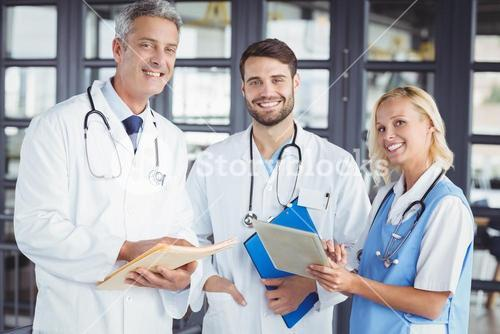 Portrait of smiling senior doctor with coworkers