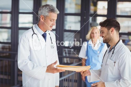 Male doctor giving document to senior