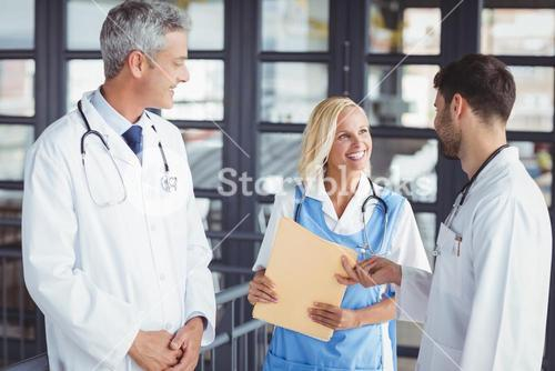 Male doctor giving document to coworker